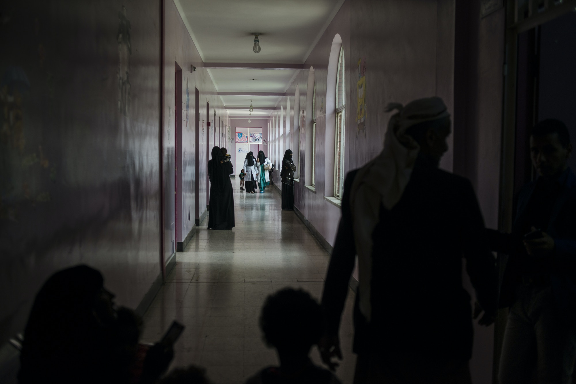 Yemeni families and nurses walk through the malnutrition wing at Sabaeen Hospital in Sanaa on May 4, 2018. Most hospitals in the north are functioning at a minimal levels, constantly short on supplies, while their staff have remained unpaid for months. Photo: Alex Potter for The Intercept
