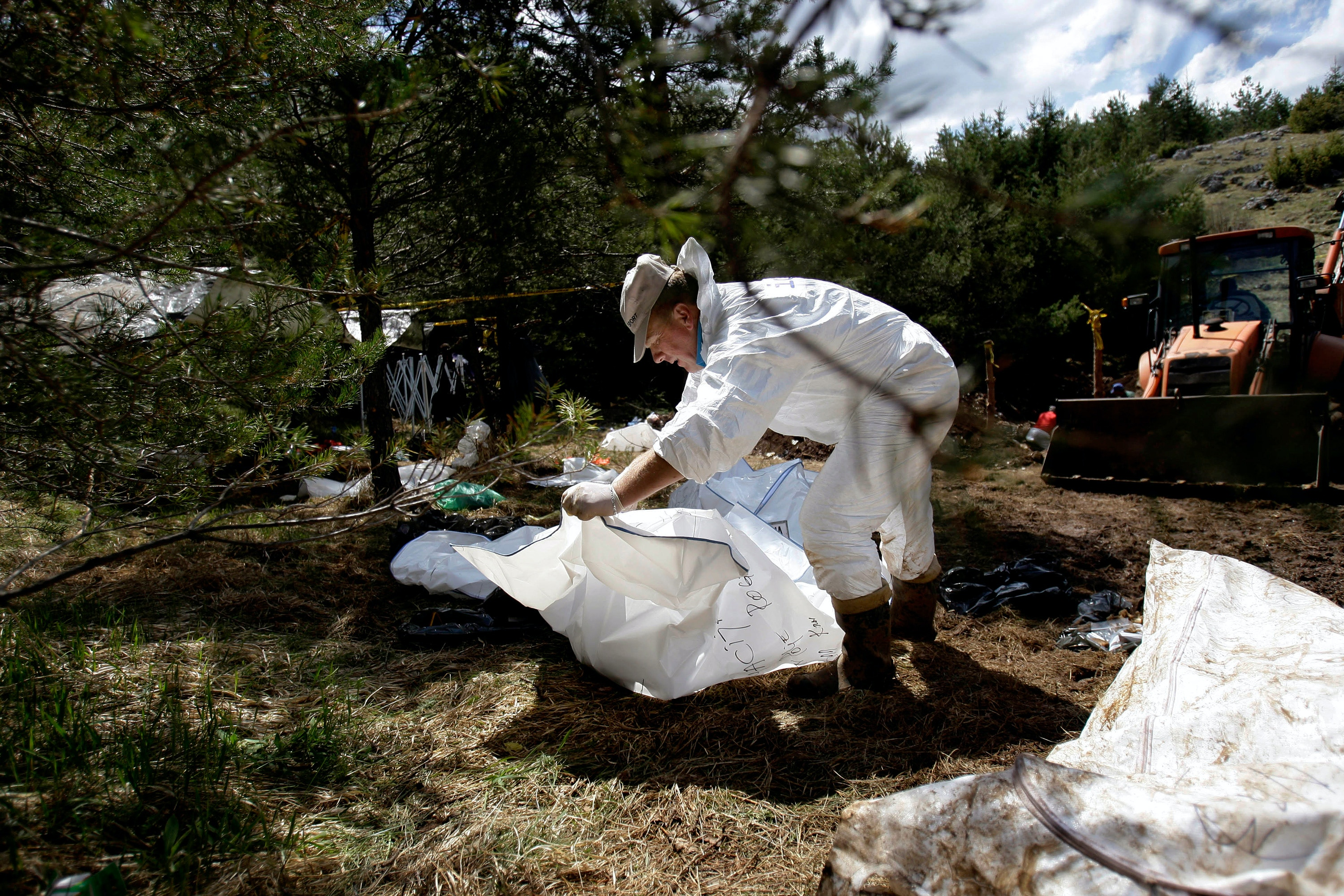 Bosnian forensic technician sorts packages containing human remains found in a mass grave in the village of Ivan Polje near Eastern Bosnian town of Rogatica, 70 kms east of Sarajevo, on Tuesday, May 10, 2011. Forensic experts believe that this mass-grave may contain dozens of remains believed to be those of Bosnian Muslims from Rogatica area killed in 1992 at the beginning of war in Bosnia.(AP Photo/Amel Emric)
