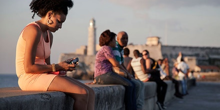 A woman uses her cellphone as she sits on the Malecon in Havana, Cuba. Image credit: Franklin Reyes/AP
