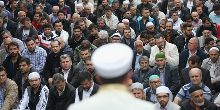 German Interior Minister Thomas de Maiziere joins Muslims protesting against the Islamic State (IS) following Friday midday prayers on September 19, 2014 in Berlin, Germany. Muslims across cities in Germany followed a call by the country's Central Council of Muslims to protest against the ongoing violence by IS fighters in Syria and Iraq.