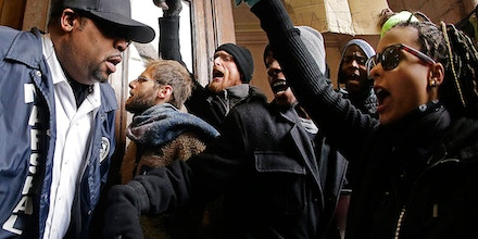Protesters confront a law enforcement officer as they try to enter City Hall Wednesday, Nov. 26, 2014, in St. Louis. Several people protesting the Ferguson grand jury decision stormed into City Hall in St. Louis on Wednesday, leading police to lock down the building and to call in more than a hundred additional officers. At least two people were arrested after the incident, in which the protesters shouted
