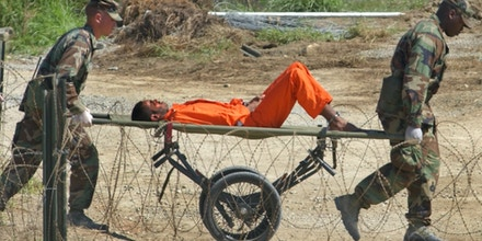 ** FILE **  In this Feb. 2, 2002 file photo, a suspected al-Qaida or Taliban detainee from Afghanistan is carried on a stretcher before being interrogated by military officials at the detention facility Camp X-Ray on Guantanamo Bay U.S. Naval Base in Cuba. President Barack Obama began overhauling U.S. treatment of terror suspects, signing orders on Thursday, Jan. 22, 2009, to close the Guantanamo Bay detention center.  (AP Photo/Lynne Sladky, File)