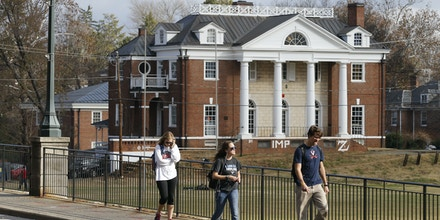 FILE - In this Monday, Nov. 24, 2014, file photo, University of Virginia students walk to campus past the Phi Kappa Psi fraternity house at the University of Virginia in Charlottesville, Va. Rolling Stone is casting doubt on the account it published of a young woman who says she was gang-raped at a Phi Kappa Psi fraternity party at the school, saying there now appear to be discrepancies in the student's account. (AP Photo/Steve Helber, File)