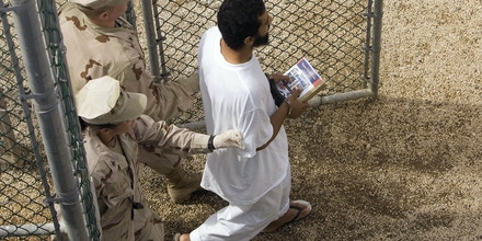 FILE - In this Nov. 18, 2008 file photo, reviewed by the U.S. Military, a female guard, bottom, and male guard escort a detainee who carries a book from the detainee library trailer to the detention facility in an open air common area at Camp Delta 4 on the U.S. Military Base in Guantanamo Bay, Cuba. Some prisoners in the highest-security unit of the Guantanamo Bay detention center have launched a protest against what they consider the religiously offensive use of female guards to move them around the U.S. base in Cuba, lawyers for the men say. (AP Photo/Brennan Linsley, File)