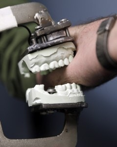 In this April 17, 2013 photo, Peter Bush, Research Scientist at the University at Buffalo,  demonstrates a modified Vise-Grip tool attached to a dental mold that is used for test bites in skin, at the school in Buffalo, N.Y. Bite marks, long accepted as criminal evidence, now face doubts about reliability.  (AP Photo/David Duprey)