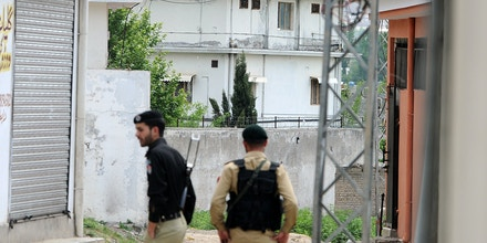 A Pakistani soldier and policeman stand in a cordoned-off street near the final hideout of slain Al-Qaeda chief Osama Bin Laden in Abbottabad on May 11, 2011, where bin Laden was killed in a US Naval Commandos special operation. Three Pakistani lawmakers offered prayers for Osama bin Laden in parliament a week after US commandos killed the Al-Qaeda leader in a covert raid near the capital, a lawmaker said.  The Saudi-born terror mastermind was killed by Navy SEALs in the garrison town of Abbottabad, where he may have lived for five years, in a raid that has raised tensions between Islamabad and Washington. AFP PHOTO/ AAMIR QURESHI (Photo credit should read AAMIR QURESHI/AFP/Getty Images)