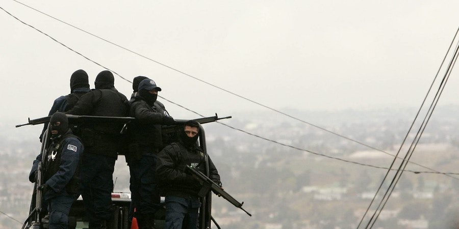 Armed police officials patrol a neighborhood in Tijuana, Mexico, Monday, Jan. 21, 2008. Mexican federal police found an underground shooting range and an arsenal of arms Saturday in this house in downtown Tijuana, which they say was a training ground for drug cartel hit men.  (AP Photo/Gregory Bull)