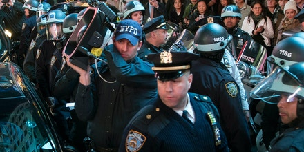 A police officer holds a Long Range Acoustic Device (LRAD), or sound cannon, as they block protestors on a march through Times Square during a protest against a grand jury's decision on Monday not to indict Ferguson police officer Darren Wilson in the shooting of Michael Brown, Tuesday, Nov. 25, 2014, in New York. The grand jury's decision has inflamed racial tensions across the U.S.  (AP Photo/John Minchillo)