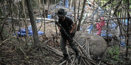 An armed Royal Malaysian Police walks at an abandoned migrant camp used by people-smugglers in a jungle at Bukit Wang Burma in the Malaysian northern state of Perlis, which borders Thailand, on May 26, 2015. Malaysian police May 26 began the grisly job of exhuming dozens of graves found in a series of remote human-trafficking camps along the Thai border in the latest grim turn in the region's migrant crisis. Police said May 25 they had found 139 grave sites and 28 abandoned detention camps used by people-smugglers and capable of housing hundreds, laying bare the grim extent of the region's migrant crisis. AFP PHOTO / MOHD RASFAN        (Photo credit should read MOHD RASFAN/AFP/Getty Images)
