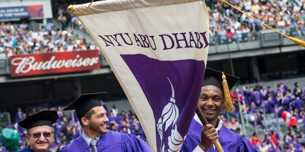 NEW YORK, NY - MAY 21:  A man carries a New York University (NYU) Abu Dhabi flag during the commencement ceremonies for New York University at Yankee Stadium on May 21, 2014 in the Bronx borough of New York City. NYU has recently been embroiled in a scandal over poor living conditions of workers building a new campus for NYU in Abu Dhabi, U.A.E. Janet Yellen, Chair of the Board of Governors of the Federal Reserve System, received an honorary doctorate and was the 2014 commencement speaker.  (Photo by Andrew Burton/Getty Images)