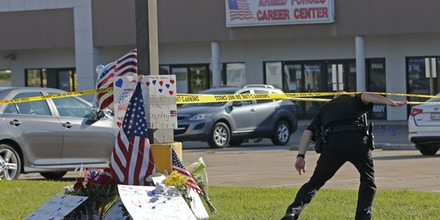 A police officer ducks under tape near a memorial in front of an Armed Forces Career Center on Thursday, July 16, 2015, in Chattanooga, Tenn. A gunman unleashed a barrage of fire at the center and another U.S. military site a few miles apart in Chattanooga, killing several and sending service members scrambling for cover as bullets smashed through the windows. The attacker was also killed. (AP Photo/John Bazemore)