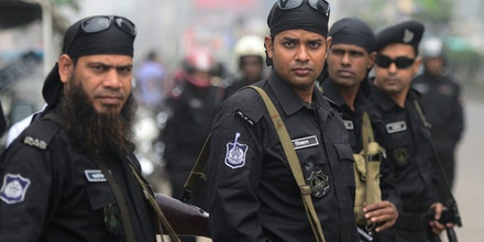 Rapid Action Battalion (RAB) personnel stand guard during a nationwide strike in Dhaka on February 18, 2013.  One protester was shot dead as police fired rubber bullets at Islamists in a eastern town as a strike enforced by Bangladesh's largest Islamic party crippled life across the nation. AFP PHOTO/ Munir uz ZAMAN        (Photo credit should read MUNIR UZ ZAMAN/AFP/Getty Images)