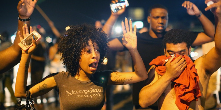 FERGUSON, MO - AUGUST 17:  Demonstrators protesting the killing of teenager Michael Brown by a Ferguson police officer try to stand their ground despite being overcome by tear gas on  August 17, 2014 in Ferguson, Missouri. Despite the Brown family's continued call for peaceful demonstrations, violent protests have erupted nearly every night in Ferguson since his death.  (Photo by Scott Olson/Getty Images)