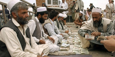 KABUL, AFGHANISTAN:  TO GO WITH AFP STORY Afghan men (R) get Afghanis, the Afghan currency, from US dollars from money changers at an outside market in Kabul, 20 September 2004.  Three weeks ahead of Afghanistan's first presidential elections, governor of Afghanistan's central bank Anwar Ul-Haq Ahady said that whether front-runner President Hamid Karzai was re-elected or a new leader entered office the country would continue to build on the financial foundations he had laid down.    AFP PHOTO/ Shah Marai  (Photo credit should read SHAH MARAI/AFP/Getty Images)