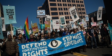 WASHINGTON, DC - OCTOBER 26, 2013:  Protesters march through downtown Washington D.C. during the Stop Watching Us Rally protesting surveillance by the U.S. National Security Agency, on October 26, 2013, in front of the U.S. Capitol building in Washington, D.C.  The rally began at Union Station and included a march that ended in front of the U.S. Capitol building and speakers such as author Naomi Wolf and former senior National Security Agency senior executive Thomas Drake. (Photo by Allison Shelley/Getty Images)