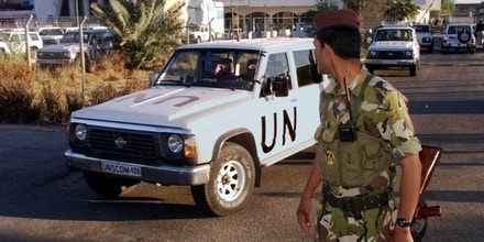An Iraqi soldier stands guard as a convoy of three cars carrying UNSCOM weapons inspectors leaves the United Nations headquarters compound in Baghdad, Wednesday, November 18, 1998 for their first mission since their return to Iraq. Eighty-six inspectors from the U.N. Special Commission, known as UNSCOM, and the International Atomic Energy Agency returned Tuesday after Iraq's decision Saturday to allow them to resume work.(AP Photo/Jockel Finck)