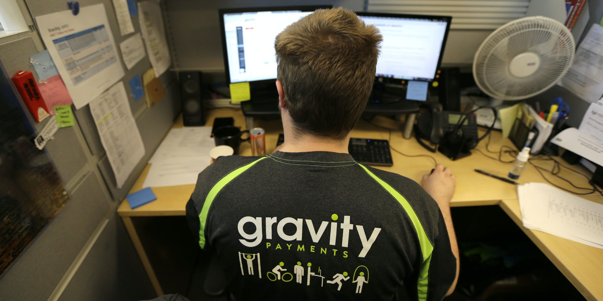 Austin Roos, a support team supervisor, works at his desk Wednesday, April 15, 2015, at Gravity Payments, a credit card payment processor based in Seattle. Gravity CEO Dan Price told his employees this week that he was cutting his roughly $1 million salary and using company profits so they would each earn a base salary of $70,000, to be phased in over three years. (AP Photo/Ted S. Warren)