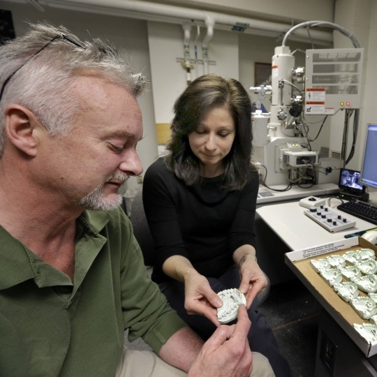 In this April 17, 2013 photo, Peter Bush and Mary Bush, Research Scientists at the University at Buffalo, pose for a photo with a dental mold, at the school in Buffalo, N.Y. Bite marks, long accepted as criminal evidence, now face doubts about reliability. (AP Photo/David Duprey)