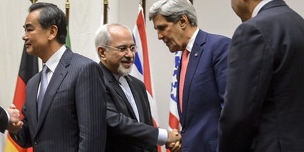 Iranian Foreign Minister Mohammad Javad Zarif (2nd L) shakes hands with US Secretary of State John Kerry next to Chinese Foreign Minister Wang Yi (far L) and French Foreign Minister Laurent Fabius (far R) after a statement on early November 24, 2013 in Geneva. World powers on November 24 agreed a landmark deal with Iran halting parts of its nuclear programme in what US President Barack Obama called