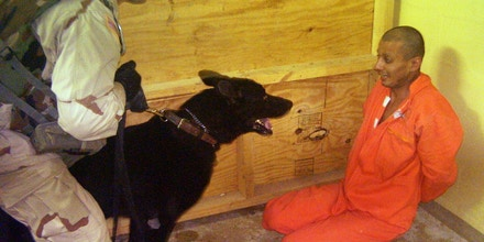 ** ** HOLD FOR RELEASE UNTIL 12:01 A.M. EDT, WEDNESDAY, JUNE 18, 2008 ** ** **  FILE ** This file image obtained by The Associated Press shows Sgt. Michael Smith, left, with his dog Marco, watching a detainee at an unspecified date in 2003 at the Abu Ghraib prison in Baghdad, Iraq. Years after being released by the U.S. military, former detainees held in Abu Ghraib and Guantanamo Bay Naval Base are suffering debilitating injuries and mental disorders from their interrogation and alleged torture, according to a new report by a human rights group. (AP Photo/File)