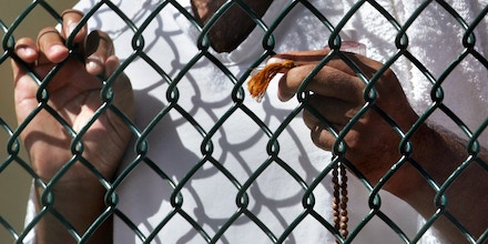 FILE - In this Sept. 19, 2006 file photo, reviewed by a U.S. Department of Defense official, a detainee stands at a fence holding Islamic prayer beads in Camp Delta detention facility at the Guantanamo Bay U.S. Naval Base in Cuba. Open for 10 years on Wednesday Jan. 11, 2012 the Guantanamo Bay prison seems more established than ever. The deadline set by President Barack Obama to close it came and went two years ago. No detainee has left in a year because of restrictions on transfers, and indefinite military detention is now enshrined in U.S. law. Prisoners at the U.S. base in Cuba plan to mark the day with sit-ins, banners and a refusal of meals, said Ramzi Kassem, a lawyer who represents seven inmates. (AP Photo/Brennan Linsley, File)