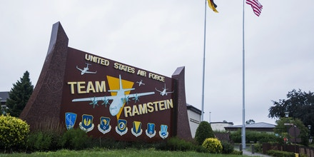 The flags of the United States and Germany fly behind a sign at Ramstein Air Base, Germany Wednesday, July 30, 2014. (AP Photo/Lucas Jackson, Pool)