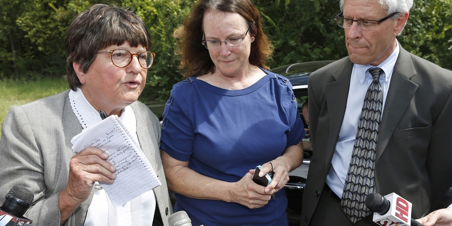 Kathleen Lord, center, and Don Knight, right, two of Richard Glossip's defense attorneys, look on as Sister Helen Prejean, left, addresses the media outside the Oklahoma State Penitentiary in McAlester Okla., Wednesday, Sept. 16, 2015, after a stay was issued for Glossip. Glossip was twice convicted of ordering the killing of Barry Van Treese, who owned the Oklahoma City motel where he worked. His co-worker, Justin Sneed, was convicted of fatally beating Van Treese and was a key prosecution witness in Glossip's trials. (AP Photo/Sue Ogrocki)