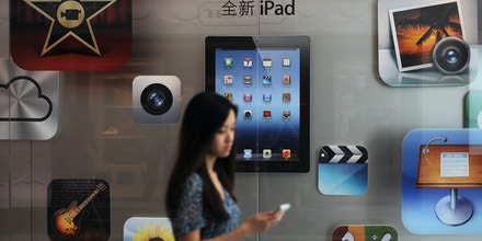 A customer passes an Apple store where the latest version of the Apple iPad went on sale in Apple stores in Shanghai on July 20, 2012.  Apple began selling the latest version of its market-leading iPad in China, on the heels of Apple paying 60 million USD to end a dispute over the iPad name in China, giving the US tech giant more certainty in selling its tablet computer in the huge market.      AFP PHOTO / Peter PARKS        (Photo credit should read PETER PARKS/AFP/GettyImages)