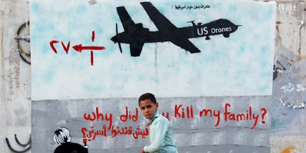 A Yemeni boy (C) walks past a mural depicting a US drone and reading