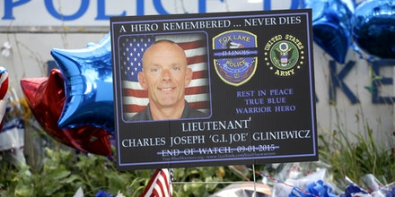 A memorial is in place at the Fox Lake Police Department on Wednesday, Sept. 2, 2015, in Fox Lake, Ill. for slain officer, Lt. Charles Joseph Gliniewicz. Gliniewicz was shot and killed Tuesday morning while pursuing a group of suspicious men. Authorities broadened the hunt Wednesday for three suspects wanted in the fatal shooting the popular Illinois police officer. (AP Photo/Nam Y. Huh)