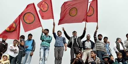 Kurdish people wave Kurdistan Workers' Party (PKK) flags while attending a funeral ceremony for YPG (People's Protection Units) fighters in the town of Suruc, Sanliurfa province, on October 14, 2014. Turkish jets bombed targets of the Kurdistan Workers' Party (PKK) in southeast Turkey, officials said on October 14, the first strikes on the outlawed group since a 2013 ceasefire amid growing concern about the peace process. AFP PHOTO / ARIS MESSINIS        (Photo credit should read ARIS MESSINIS/AFP/Getty Images)