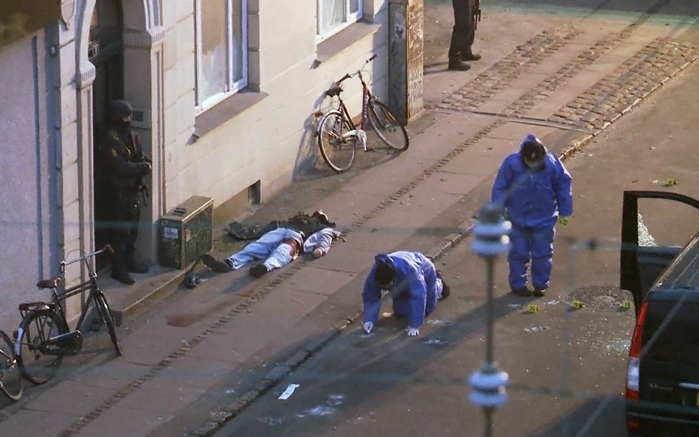 In this image made from TV The lifeless body of a shooting suspect lays on the pavement as Danish police forensic officers examine the scene after Danish police shot and killed the man early Sunday suspected of carrying out shooting attacks at a free speech event and then at a Copenhagen synagogue, in Copenhagen Sunday, Feb. 15, 2015.  The suspect is not yet identified by police. A man opened fire Saturday killing a Danish documentary filmmaker and a member of the Scandinavian country's Jewish community and wounding five police officers in the attacks. (AP Photo / TV2 Norway) NORWAY OUT - DENMARK OUT - TV OUT