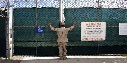U.S. NAVAL BASE GUANTANAMO, CUBA - JUNE 1:  (EDITORS NOTE: IMAGE REVIEWED BY U.S. MILITARY PRIOR TO TRANSMISSION) A guard stands outside the gate of Camp Iguana detention facility, which houses the Chinese Uighur Guantanamo detainees June 1, 2009 at U.S. Naval Base Guantanamo Bay, Cuba.  Seventeen Uighur detainees at Guantanamo are cleared for release but continue to be held because China considers them terrorists and has indicated they will be incarcerated if they return.  (Photo by Brennan Linsley-Pool/Getty Images)