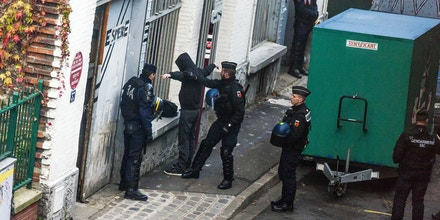 Police officers search a man during a Police and Gendarmerie raid in a building believed to be squatted in Le Pre Saint-Gervais, northeast of Paris on November 27, 2015.  A search was conducted in the morning of November 27 at a squat in Le Pre-Saint-Gervais, occupied by people suspected of intent to