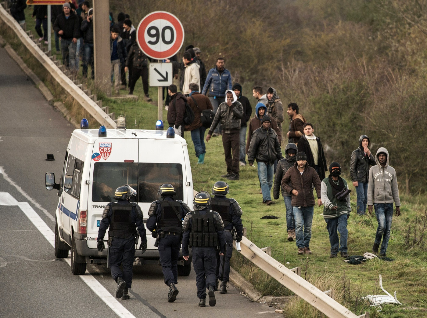 "French riot police block migrants and refugees from boarding trucks on the circular bypass in front of the migrant camp known as ""the Jungle"" near the northern port of Calais, on November 25, 2015 where some 4500 people live. / AFP / PHILIPPE HUGUEN        (Photo credit should read PHILIPPE HUGUEN/AFP/Getty Images)"