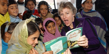 Image #: 1682524    U.S. State Department's top official for public diplomacy Karen Hughes (R) reads a book with Kashmiri earthquake survivors during her visit at a tent school in Muzaffarabad, Pakistan, November 14, 2005. NATO forces set up winter shelters high in the mountains of Pakistan's earthquake zone on Monday, as doctors rushed to immunize children against measles and other diseases before snows cut off remote areas. REUTERS/Achmad Ibrahim/Pool /Landov
