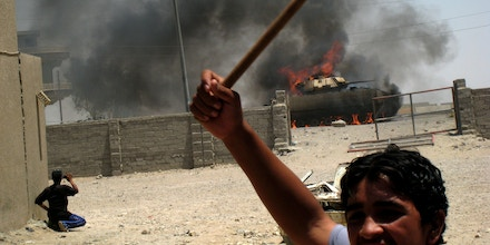 An Iraqi youth reacts as a US military's Bradley fighting vehicle is on flames in Obeidi, in south east Baghdad, Iraq,  Monday, July 2, 2007, after it was struck by a road side bomb, according to eyewitnesses. There were no reports on possible casualties. (AP Photo)