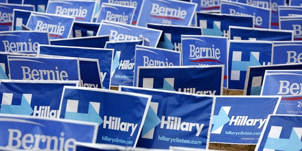 Campaign signs for senator Bernie Sanders, an independent from Vermont and 2016 Democratic presidential candidate, not pictured, and Hillary Clinton, former Secretary of State and 2016 Democratic presidential candidate, not pictured, cover a lawn before the Democratic presidential candidate debate in Charleston, South Carolina, U.S., on Sunday, Jan. 17, 2016. Hours before Sundays Democratic debate, the two top Democratic contenders held a warm-up bout of sorts in multiple separate appearances on political talk shows, at a time when the polling gap between the pair has narrowed in early-voting states. Photographer: Patrick T. Fallon/Bloomberg via Getty Images