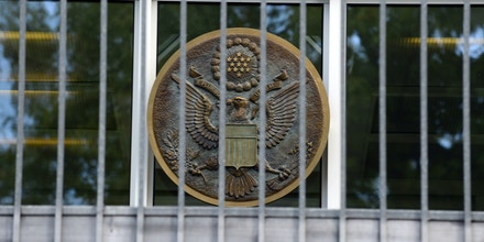 An emblem of the US Embassy in Berlin's Clayallee is pictured on September 13, 2012, after emergency services evacuated the visa section of the consulate. According to the police an employee felt difficulty breathing after she opened the passport of a visitor applying for visa. The workers at the consulate later returned to their posts. The incident occured only two days after US mebassy and consulate buildings were attacked across the Middle East.  AFP PHOTO / JOHN MACDOUGALL        (Photo credit should read JOHN MACDOUGALL/AFP/Getty Images)