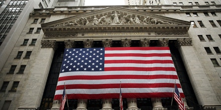 NEW YORK, NY - JULY 08: An American flag hangs on the New York Stock Exchange (NYSE) building at the close of the day after trading was paused for nearly four hours due to a