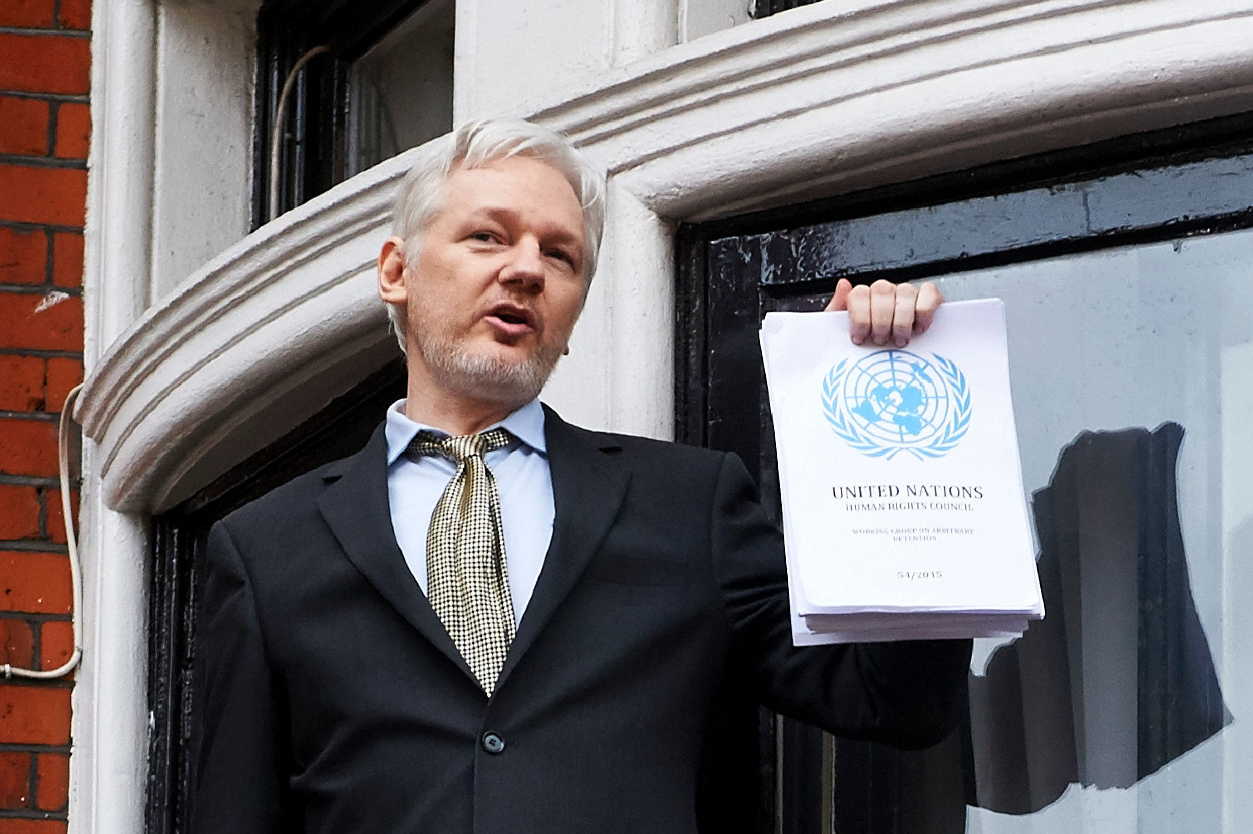 "WikiLeaks founder Julian Assange addresses the media holding a printed report of the judgement of the UN's Working Group on Arbitrary Detention on his case from the balcony of the Ecuadorian embassy in central London on February 5, 2016.During a press conference on February 5 Julian Assange, speaking via video-link, called for Britain and Sweden to ""implement"" a UN panel finding saying that he should be able to walk free from Ecuador's embassy, where he has lived in self-imposed confinement since 2012. / AFP / NIKLAS HALLE'N (Photo credit should read NIKLAS HALLE'N/AFP/Getty Images)"