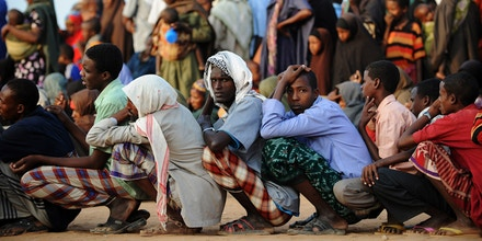 Somali men wait in line outside a registration and food distribution point in the Dadaab refugee camp in northeastern Kenya on July 5, 2011. Dadaab, a complex of three settlements, is the world's largest refugee camp. Built to house 90,000 people and home to more than four times that number, it was already well over its maximum capacity before an influx of 30,000 refugees in June. Upon arrival, the refugees find themselves tackling a chaotic system that sees new arrivals go days, even weeks, without food aid.