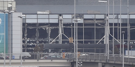 TOPSHOT - A picture taken on March 22, 2016 in Zaventem, shows the damaged facade of Brussels airport after at least 13 people were killed and 35 injured as twin blasts rocked the main terminal of Brussels airport.AFP PHOTO / JOHN THYS / AFP / JOHN THYS        (Photo credit should read JOHN THYS/AFP/Getty Images)