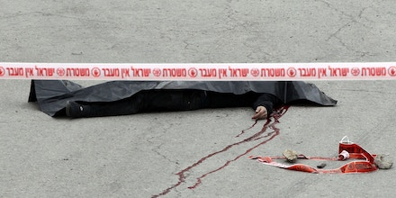 EDITORS NOTE: Graphic content / A general view shows the body of one of the two Palestinians who wounded an Israeli soldier in a knife attack before being shot dead by troops, an army spokeswoman said, at the entrance to the heavily guarded Jewish settler enclave of Tal Rumeda in the city centre of the West Bank town of Hebron on March 24, 2016.An Israeli soldier was detained after allegedly shooting a wounded Palestinian assailant in the head and killing him as he lay on the ground, the army said. In the video released by B'Tselem, an Israeli rights non-governmental organisation, the soldier appears to shoot the Palestinian again in the head without provocation as he lay wounded from a gun shot wound on the ground. / AFP / HAZEM BADER (Photo credit should read HAZEM BADER/AFP/Getty Images)