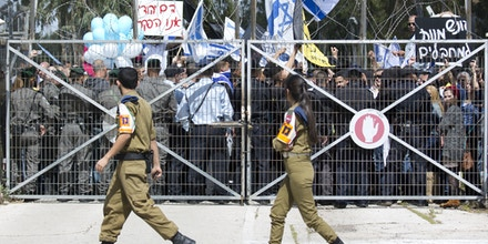 Israeli right wing protesters waves flags outside of Castina military court near the southern Israeli city of Ashkelon, Israel, Tuesday, March 29, 2016.  Some hundreds of protesters have rallied outside the court in support of a soldier filmed last week shooting dead a wounded Palestinian attacker in the West Bank, an incident that has proven divisive in Israel, where army service is mandatory. The signs say