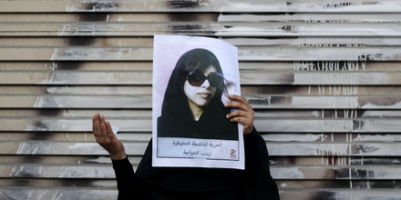 FILE - In this March 28, 2013 file photo, a Bahraini anti-government protester holds up a picture of jailed opposition human rights activist Zainab al-Khawaja as she participates in a prayer for al-Khawaja's freedom after a march in Malkiya, Bahrain. Government reforms put in place by Bahraini authorities in the wake of widespread anti-government protests four years ago have failed to end serious violations of human rights in the strategically important Gulf nation, Amnesty International said in a report released Thursday, April 16, 2015. (AP Photo/Hasan Jamali, File)