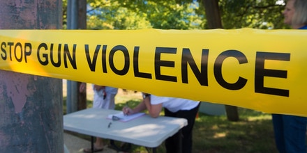 Members of the Coalition of Gun Violence Prevention sign-in behind their version of