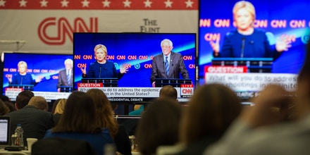 Journalists watch Democratic presidential candidates Hillary Clinton and Bernie Sanders debate on televisions in the media room at the University of Michigan in Flint, Michigan, March 6, 2016. / AFP / Geoff Robins        (Photo credit should read GEOFF ROBINS/AFP/Getty Images)