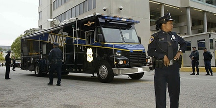 BALTIMORE, :  A police mobile command center pulls up in front of the Federal Courthouse in Baltimore, Maryland, 24 October 2002 moments before police a caravan entered the courthouse underground . Police arrested two men,  John Allen Muhammad, 42, and his 17-year-old stepson John Lee Malvo, a Jamaican national, wanted in connection with sniper attacks around the US capital that left 10 dead. A tactical team detained the two as they slept in a car on a highway rest stop in Maryland, north of Washington.    AFP PHOTO   LUKE FRAZZA (Photo credit should read LUKE FRAZZA/AFP/Getty Images)