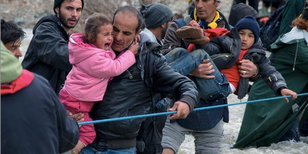 A child cries as migrants cross a river, north of Idomeni, Greece, attempting to reach Macedonia on a route that would bypass the border fence, Monday, March 14, 2016. Hundreds of migrants and refugees walked out of an overcrowded camp on the Greek-Macedonian border Monday, determined to use a dangerous crossing to head north.